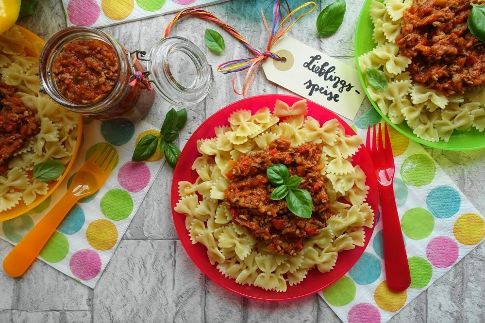 Nudeln/Pasta mit Fleischsoße und Gemüse alla bolognese; bunte Teller und Servietten
