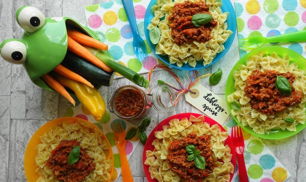 Nudeln/Pasta mit Fleischsoße alla bolognese mit viel Gemüse; bunte Teller und Servietten; Froschkönig