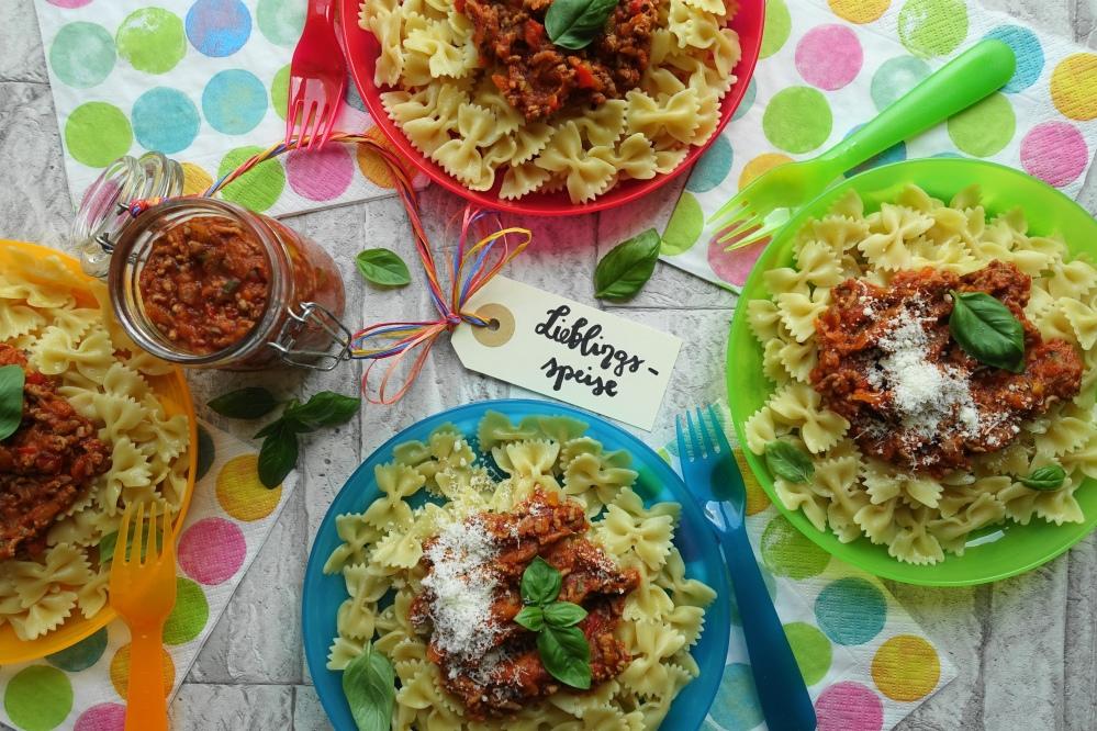 Nudeln/Pasta mit Fleischsoße für Kinder; bunte Teller und Servietten