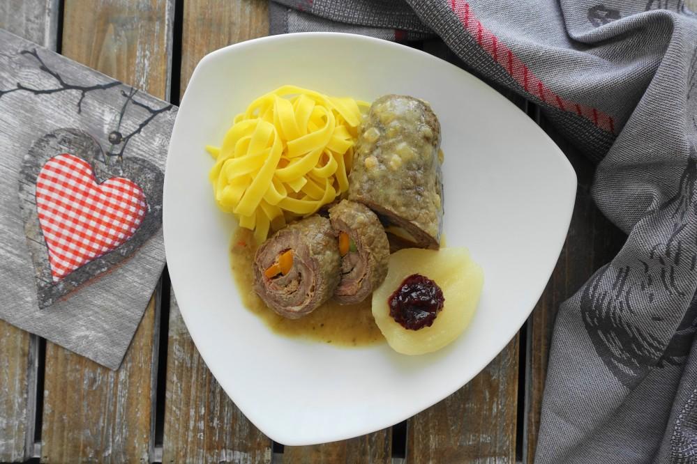 Rindsroulade in Zwiebelsoße und Bandnudeln; dazu eine halbe Birne mit Preiselbeermarmelade;